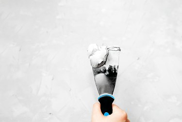 metal spatula with putty or paint with a black handle and a blue stripe in a light skinned hand against a background of light grey concrete surface