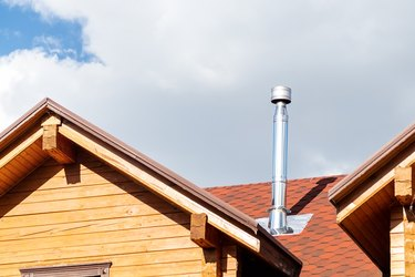 Stainless steel chimney pipe on roof of modern wooden beam cottage villa house. Home fireplace and heating exhaust system