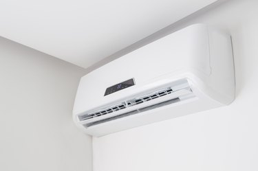 Split air conditioner closeup on white wall in flat indoors