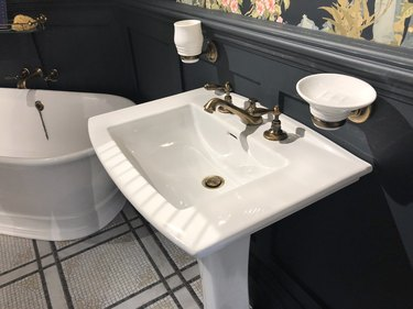 Image of luxury washroom bathroom with large freestanding bath with curved ends and bronze mixer tap, white rectangular sink wash basin with soap dish, wood panelling painted black and floral wallpaper with flowers pattern, mosaic tiled flooring tiles