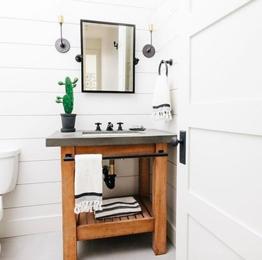 White powder room with wood vanity featuring concrete countertop and black hardware, black industrial mirror, and black and white striped towels.