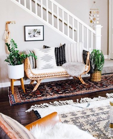 Bohemian entryway design with rattan bench and black and white patterned throw pillows, two plants, and kilim runner