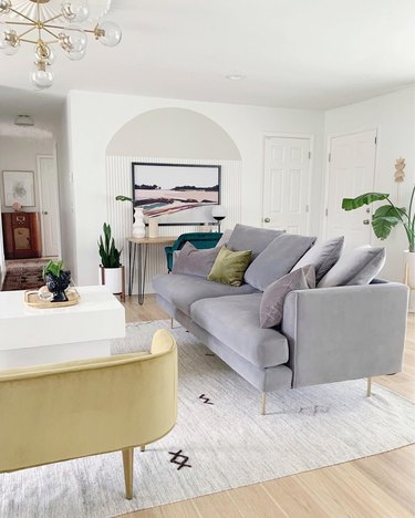 midcentury-inspired living room with gray velvet couch and yellow-green velvet rounded bench