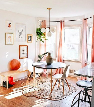 Breakfast nook with black and white midcentury dining furniture, blush curtains, and a circular jute rug.
