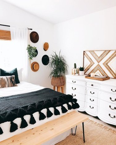 Black, white, and wood minimal bedroom with subtle bohemian accents