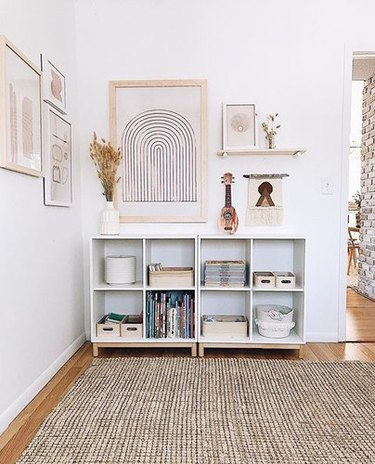 White corner with 8 cubic shelves featuring storage baskets and abstract beige rainbow print and floating shelf