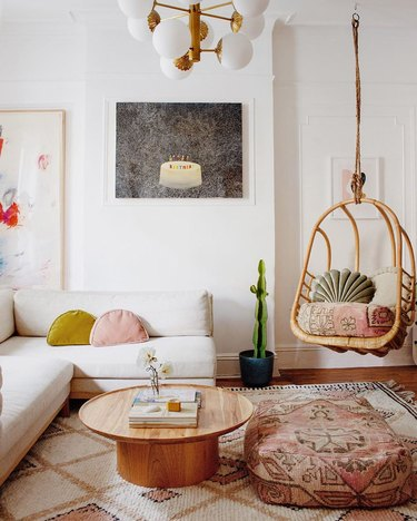 White living room with floating rattan chair, patterned oversized poufs, and white modular couch with velvet half moon throw pillows