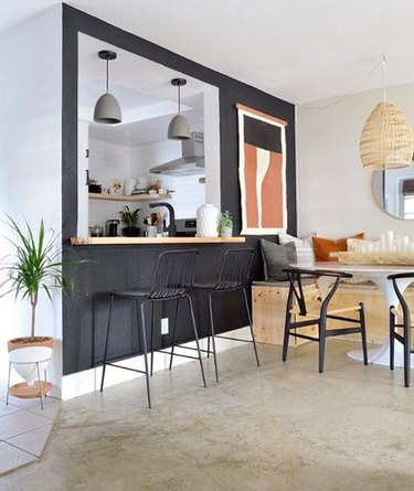 Minimal bohemian dining room with black accent wall and midcentury dining furniture