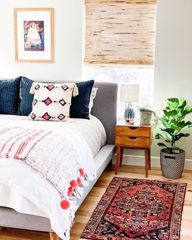 Bohemian bedroom with wooden midcentury nightstand, textured pillows, and gray headboard