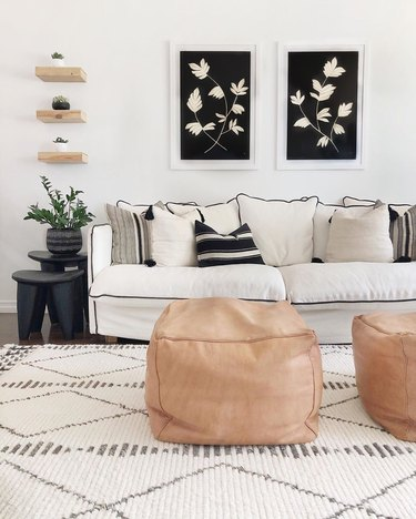 Black, white, and beige living room featuring cream couch with black piping and twin beige square leather moroccan poufs