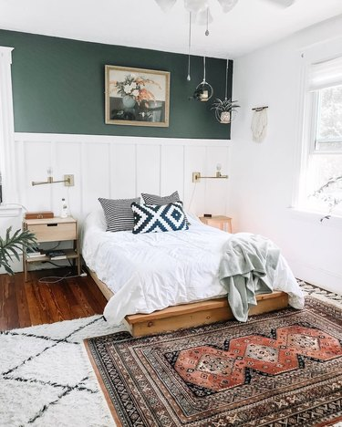 Bedroom featuring white rug with black diamond pattern underneath orange and black kilim rug. Minimal blonde wood nightstands, aztec pillow, hanging planters, and top half of wall painted green and lower half white shiplap