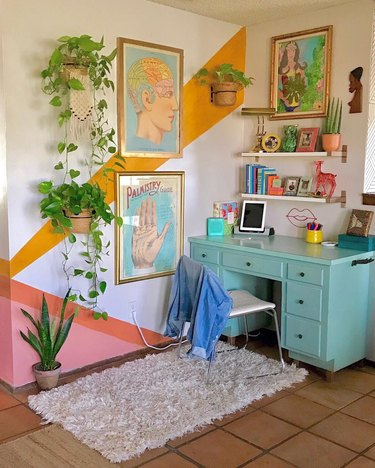 Colorful home office corner with turquoise desk, color-blocked diagonal wall paint, and white floating shelves
