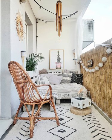 Balcony featuring lots of textiles, rattan armchair, bamboo privacy fence, and standalone fireplace