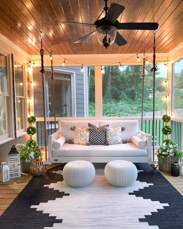 Black and white porch featuring white couch swing, geometric black-and-white rug, and Edison LED string lights.