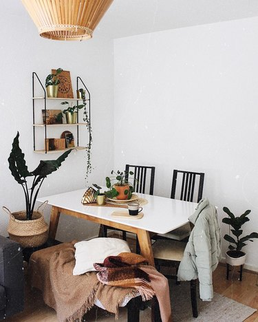 Minimal boho dining room with plants, white table, and black ladder-back chairs