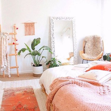 Whimsical bedroom featuring various shades of peach, wooden decorative ladder, large white floor mirror, and potted plant