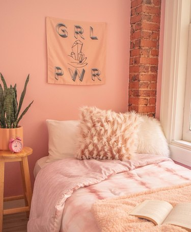 """bedroom with pink wall, wall hanging that reads """"GRL PWR"""" and bed with various pink and white bedding items"""