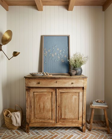 wooden cabinet with light blue artwork on top and vases with flowers nearby
