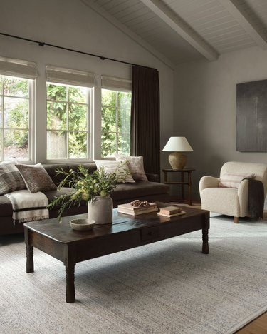 living room with dark coffee table and light rug