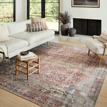 living room with white furniture and patterned rug