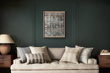 living room with dark green wall and light couch with framed art
