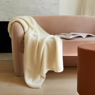 Pink couch with white throw
