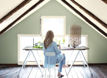person sitting at a desk with low ceiling and light green wall