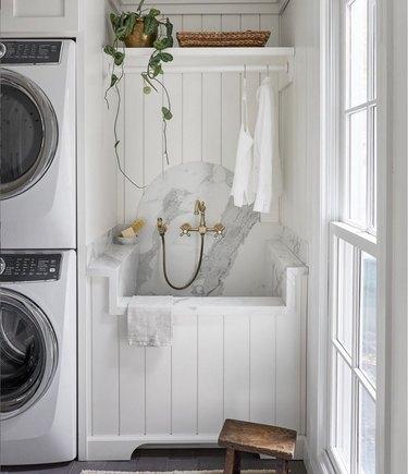 Laundry room with deep sink, handheld sprayer and marble backsplash.