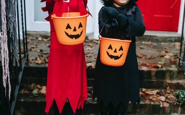 two trick or treaters with orange pumpkin buckets