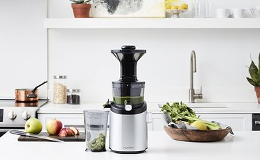 Hurom juicer with fruits and vegetables in kitchen