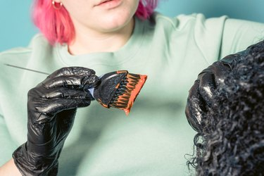 woman with pink hair dyeing black hair orange