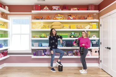 Joanna and Clea of The Home Edit standing in their rainbow prop room