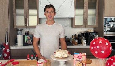 Antoni Porowski behind his specialty Betty Crocker cake for his dog, Neon.