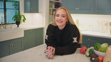 Adele leaning on counter in the her kitchen