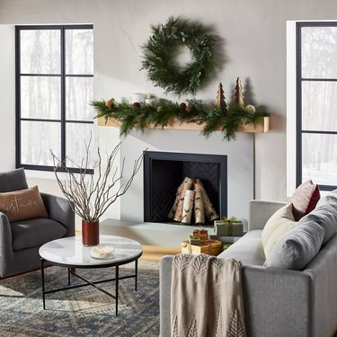 living room with wreath over fireplace and garland on mantle
