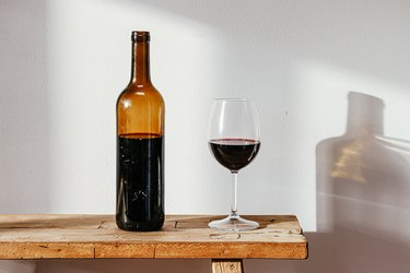 Wine bottle and glass on a wooden bench