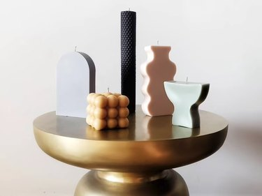 geometric candles on a gold table