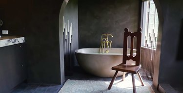 black bathroom with tub and wooden chair