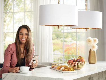 Farah Merhi on white kitchen island with two white drum lighting fixtures above the space