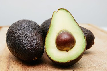 Cut avocado on a wooden cutting board