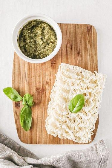 Pesto, ramen, and basil on a wooden cutting board