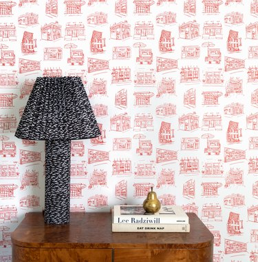 side table with books and lamp and red and white wallpaper in the background