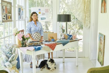 cortney novogratz at a desk with colorful fabric swatches