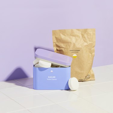 tin and paper bag of toilet bowl cleaner tablets