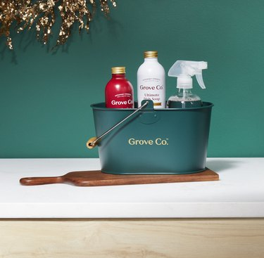 green pail holding bottles of cleaners