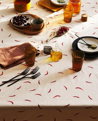 table with chili-patterned tablecloth and various dishes and linen napkins