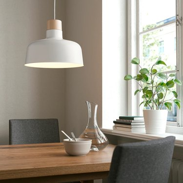 dining table with black chairs, tableware, and a white and birch pendant lamp