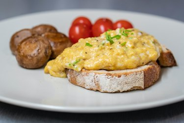 scrambled eggs on toast with tomatoes and potatoes