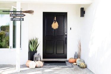 black front door with halloween decor and pumpkins