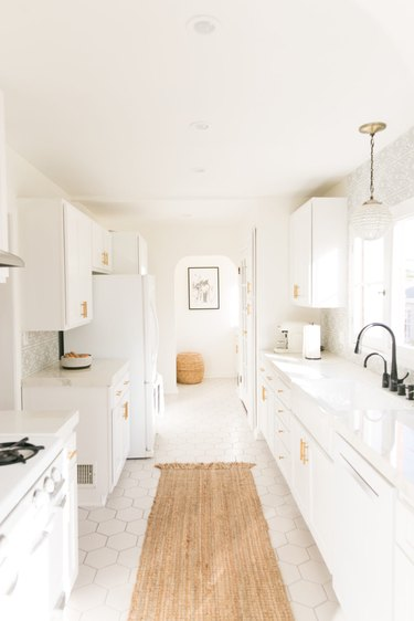 all white kitchen with sisal runner rug and gold hardware on cabinets